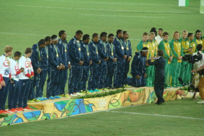 As International Olympic Committee member Princess Anne draped a gold medal around a Fijian player's neck, he knelt as a sign of respect.
