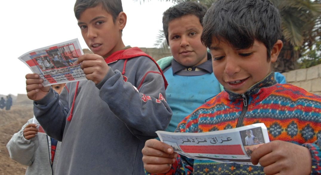 Some modern militaries distribute leaflets, such as the ones these Iraqi boys are reading, in an attempt to convince people to believe certain things or behave in a particular way.