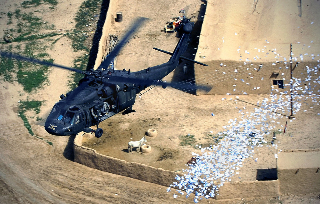 A U.S. military helicopter drops military leaflets over a village in northern Iraq in 2008.