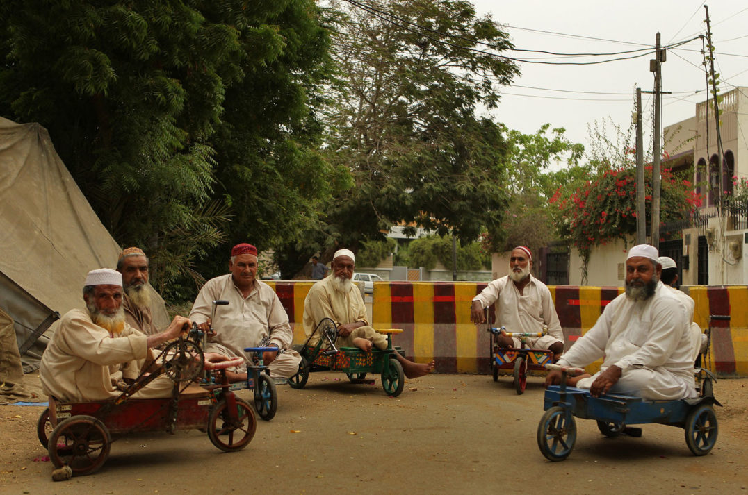 Men with lifetime paralysis from polio use bicycle carts in the streets of Karachi.