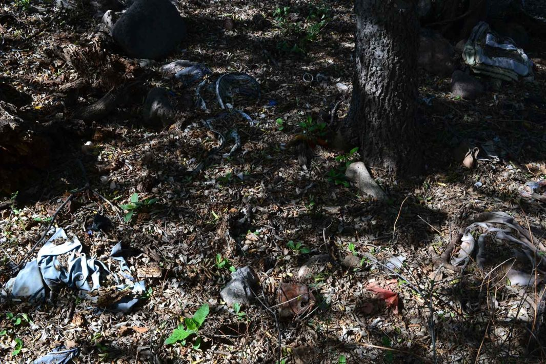 Left behind belongings blend in with the landscape as they decompose under a shade tree.