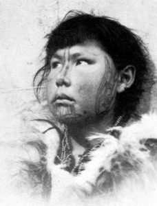 A Yupik woman, photographed in the early 1900s, bears traditional skin-stitched facial tattoos.