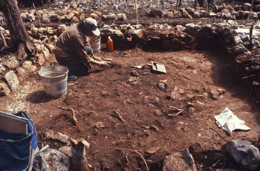 Archaeologists excavate a room of a wood-and-thatch house at Sayil, Yucatan, Mexico.