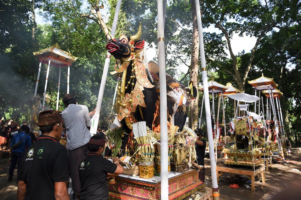 religion origins - A cremation ceremony is held in the Sacred Monkey Forest near the village of Padangtegal in Bali, where the author's investigations into plastic littering emphasized the power of belief to change behavior.