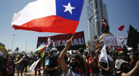 Chile democracy dignity - A protestor in 2020 in Santiago waves the Chilean flag.