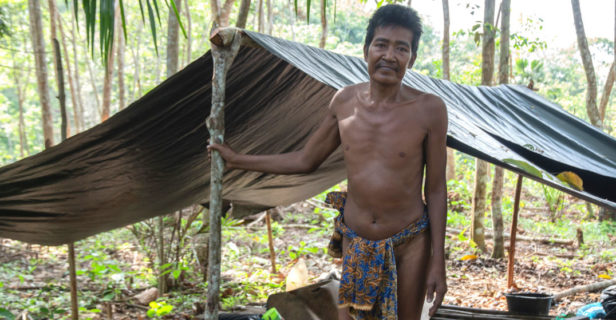 Orang Rimba covid-19 - An Orang Rimba man named Nyeruduk stands in front of a tent on a rubber plantation in Sumatra.