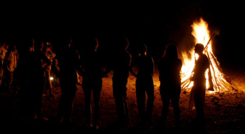 A group of people stand with their backs to the camera around a bonfire at night