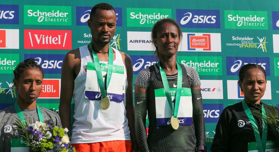Four athletes stand on a winner's podium with medals around their necks. The people on the left and right are both holding flowers.