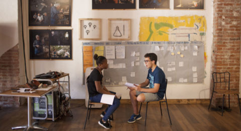 Two young people sit facing each other with paper on their laps. Behind them are large photos and a large grey storyboard.