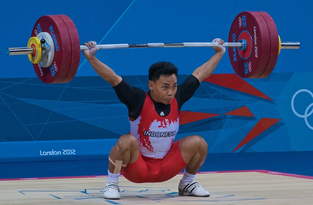 A male Olympic weightlifter snatches a weighted barbell.