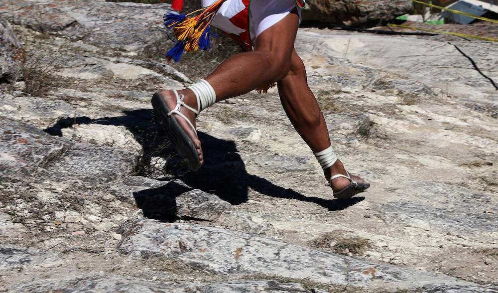 A Tarahumara person running on rock with their feet in white-laced sandals.