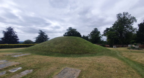A grass-covered mound, used by the Anglo-Saxons, sits surrounded by trees and hedges, with flat, concrete slabs on the ground in front of it.