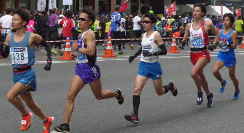 Five runners in running shorts and athletic tops are pictured mid-stride as they move down a street blocked off by orange and white pylons and bars.
