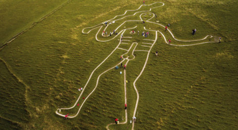 An aerial image shows a large chalk drawing of a nude man holding a large stick carved into a hill. A group of people are spread out and cleaning different parts of the chalk drawing.