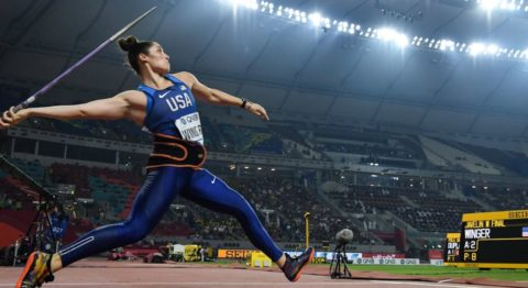 An athlete in mid-stride dressed in blue tights and a tank top prepares to throw the javelin in a large, well-lit sports arena.
