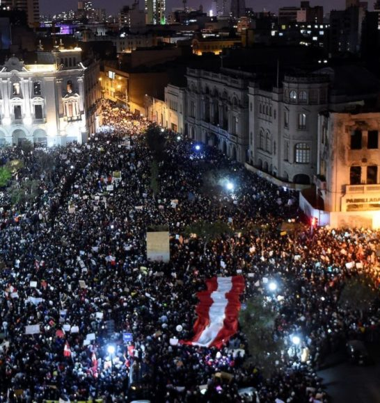 A large crowd of protestors fills a plaza and the surrounding streets at night. An enormous red and white flag floats over some of the participants.