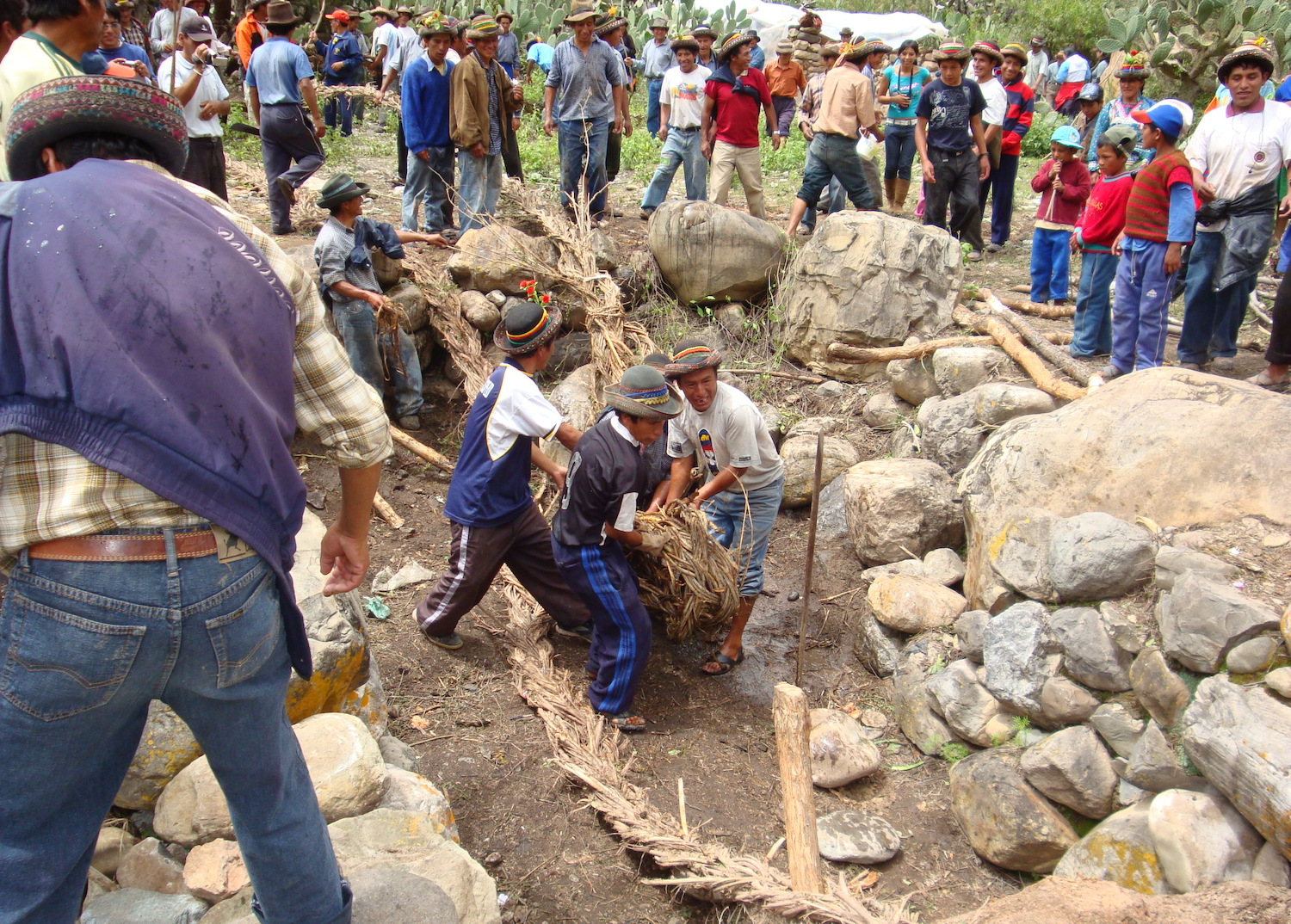 Community members look on as a group of people unfurl a long, large rope on the ground next to another rope. They are surrounded by large stones.