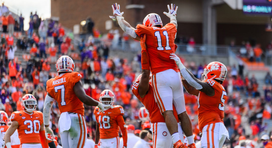 Two football players in orange and white uniforms lift their teammate in the air in celebration while surrounded by other team members.