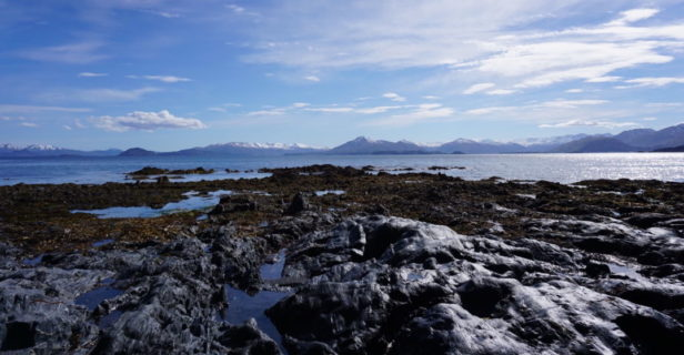 A landscape image shows a blue sky with clouds over rocks leading out to water and mountains in the distance.