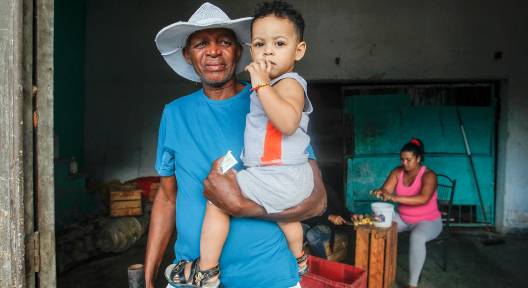 A person in a blue shirt and white, wide-brimmed hat holds a child in one arm. In the background, a person in a pink shirt sits behind a crate.