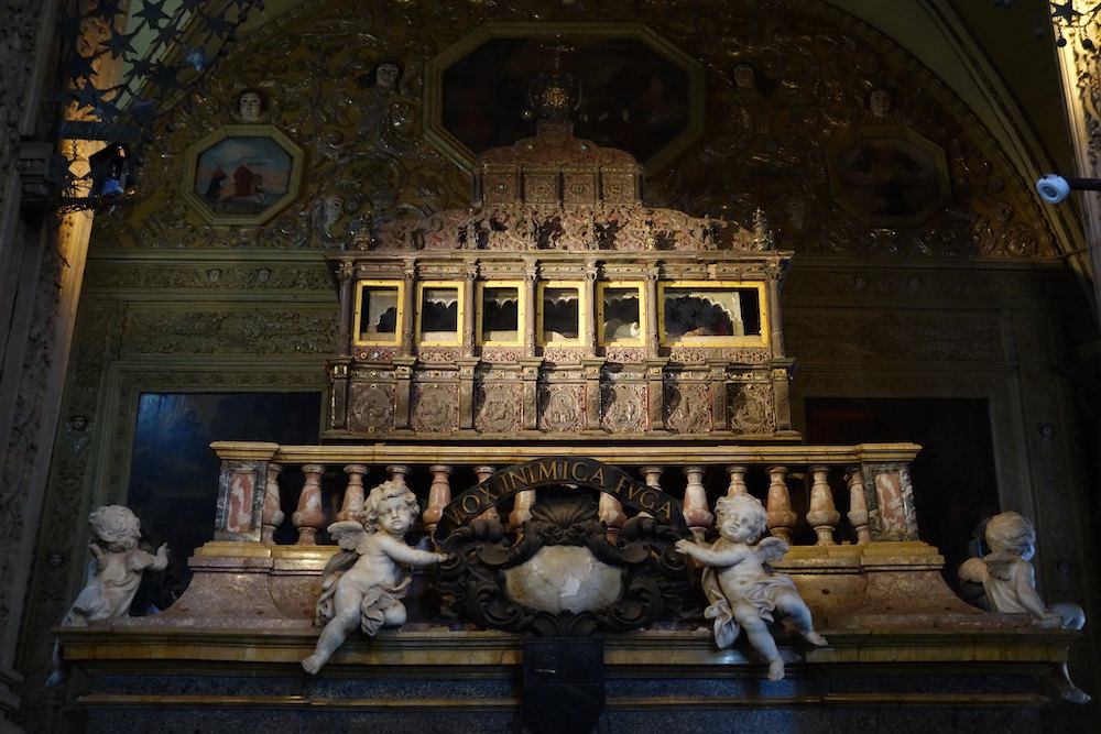 A ray of light shines onto a large upright tomb covered in intricate carvings with windows at the top and four stone cherubs holding a wreath at the base.