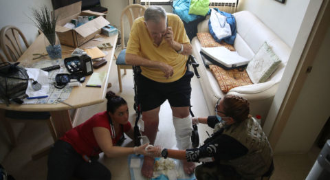 A man in an assisted living facility has his legs bandaged by two health care professionals as they prepare to evacuate him in the aftermath of Hurricane Maria.