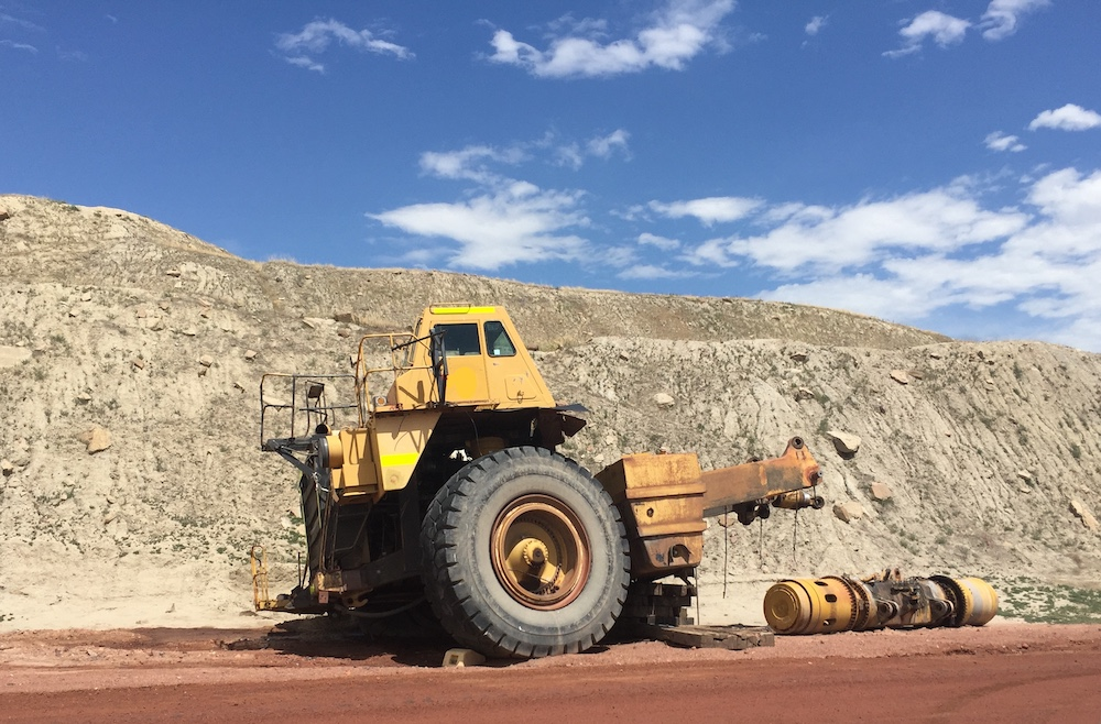A partially dismembered yellow truck cabin and a large black wheel lie on red dirt in front of a large pile of rocks.