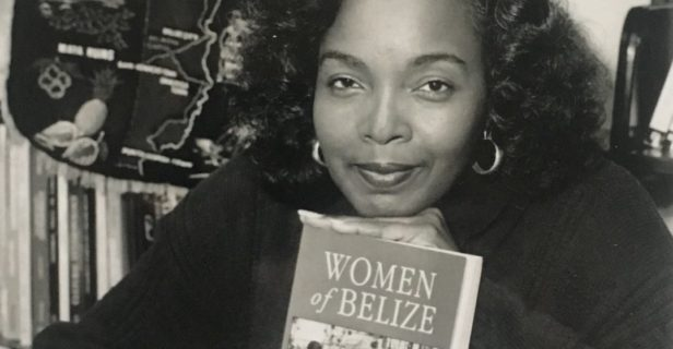A black-and-white photograph of a woman at a desk in front of a shelf of books features her resting her chin on an upright book, with other books lying flat on the table.